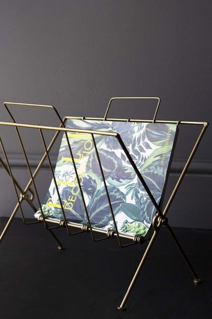 Brass Magazine Rack on dark wall background with book inside lifestyle image