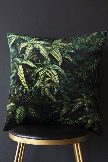 Lifestyle image of the Green Jungle Leaf Velvet Cushion on gold stool and dark wall background
