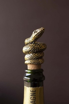 Lifestyle image of the Antique Gold Snake Bottle Stopper in a bottle with dark wall background