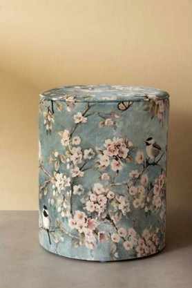 Lifestyle image of the Blue Velvet Cherry Blossom Pouffe Foot Stool on pale yellow wall and grey floor background