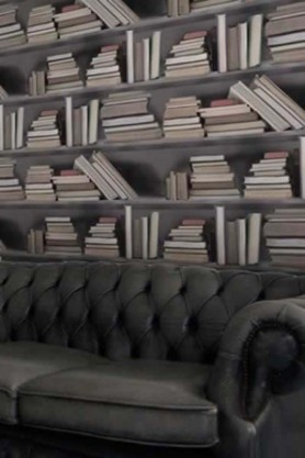 Bookshelf wallpaper with a brown leather sofa in front of it