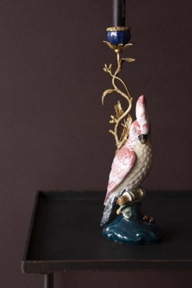 Lifestyle image of the Ceramic & Brass Cockatoo Candle Holder with tall black candle and on black side table with dark wall background