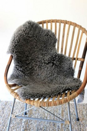 Genuine Sheepskin Rug - Curly Slate on natural rattan chair with grey floor and pale background lifestyle image