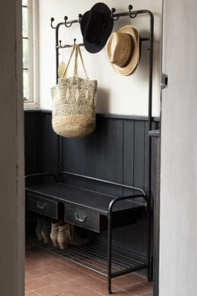 Lifestyle image of the Industrial-Style Hallway Storage Coat Rack with hats and bag hung on hooks and shoes on rach with dark panelled wood and white wall background