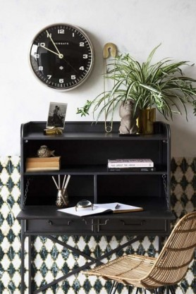 Lifestyle Image of the open Industrial-Style Bureau Sideboard Storage Cabinet & Desk with black clock and house plant filled with stationary with rattan chair on patterned wall background
