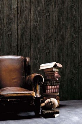 Brown leather armchair and a pile of books in front of charred wood boarding wallpaper