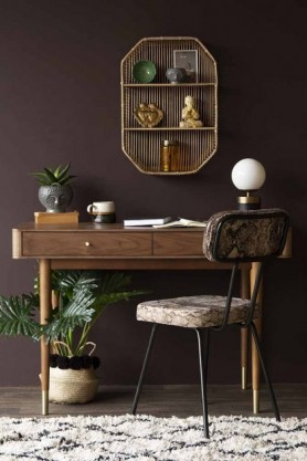Lifestyle image of the Mid-Century Design Two Drawer Desk with chair and shelving unit on monochrome rug and dark purple wall background