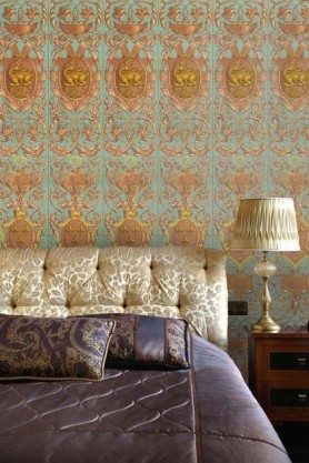 Lifestyle image of Fontainebleau wallpaper in powder blue with a bed in front if it