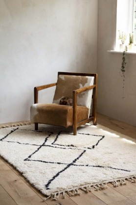 Lifestyle image of the Original Moroccan Berber Large Rug with cowhide armchair on pale wooden floor and pale wall background