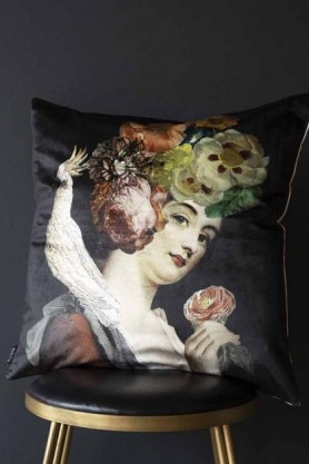 Quirky lady with floral headdress and cockatoo black velvet cushion sat on a stool