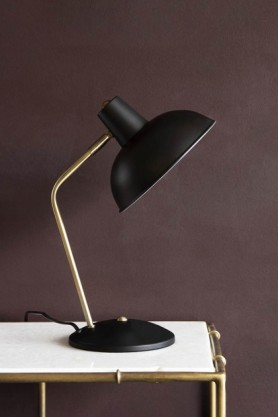 Lifestyle image of the Retro Desk Lamp - Matt Black on marble table with dark wall background