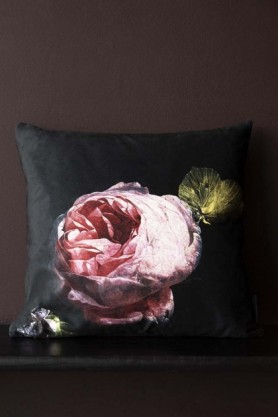 Lifestyle image of the Single Pink Rose Velvet Cushion on black bench with dark wall background