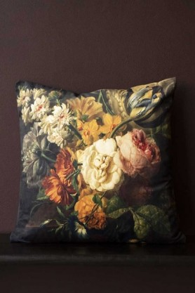 Lifestyle image of the Summer Flowers Velvet Cushion on black bench with dark wall background