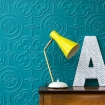 Close up of a lamp with a bright yellow shade in front of the Anaglypta Egon wallpaper painted blue - Rockett St George