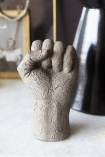 Close-up detail image of the Distressed Stone Effect Fist Hand Ornament on marble console table with black terracotta vase and gold picture frame in background