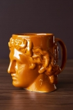 Side-on lifestyle image of the Greek Goddess Hestia Mug in Burnt Orange on dark wooden surface and dark wall background