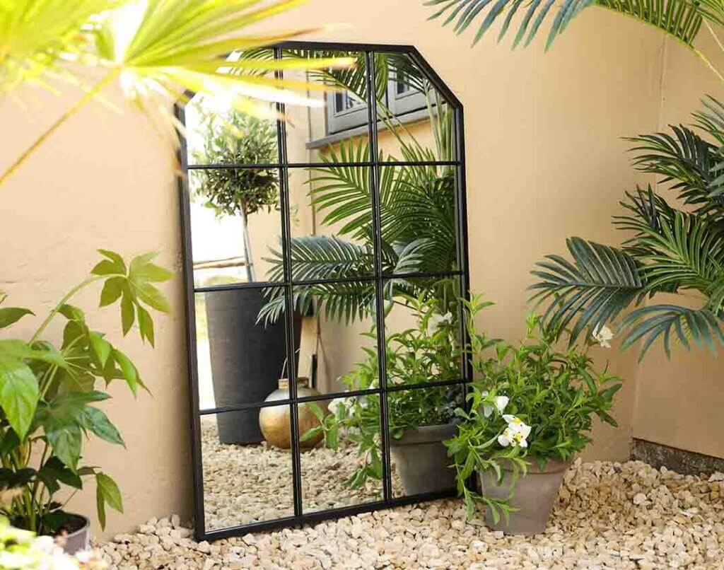 image of the outdoor metal frame garden mirror against sand coloured walls on gravel stones