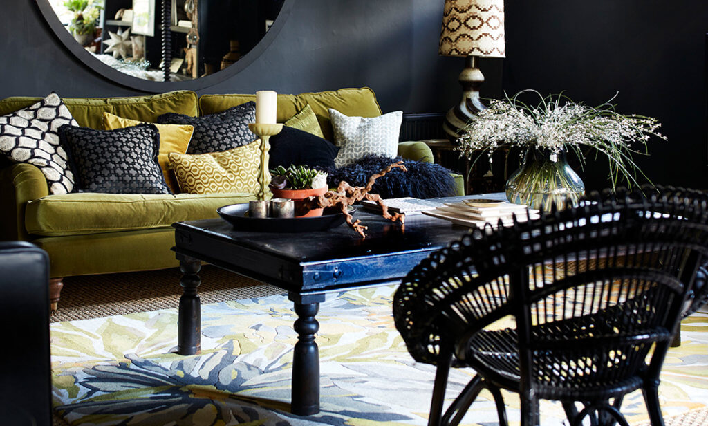 close-up image of a dark living room with a styled coffee table featuring plants, vases and candles.