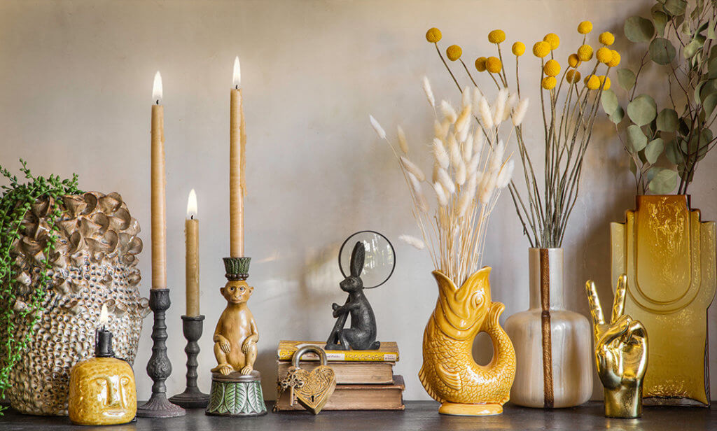 image of a collection of mustard yellow vases, quirky monkey candles, faux flowers and plants