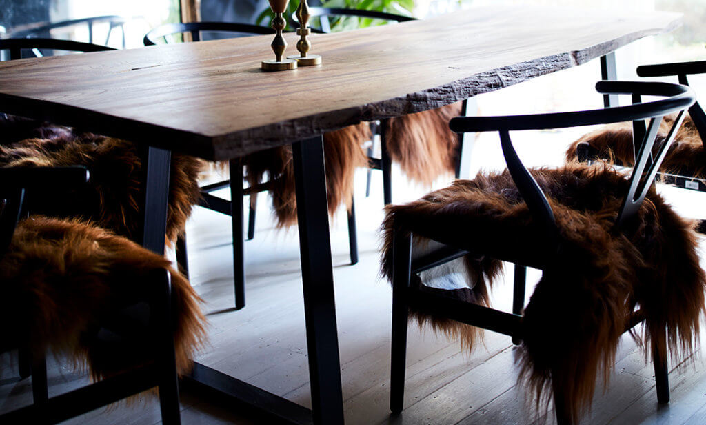 image of a dining room with a wooden table. The dining chairs are decorated with sheepskins.