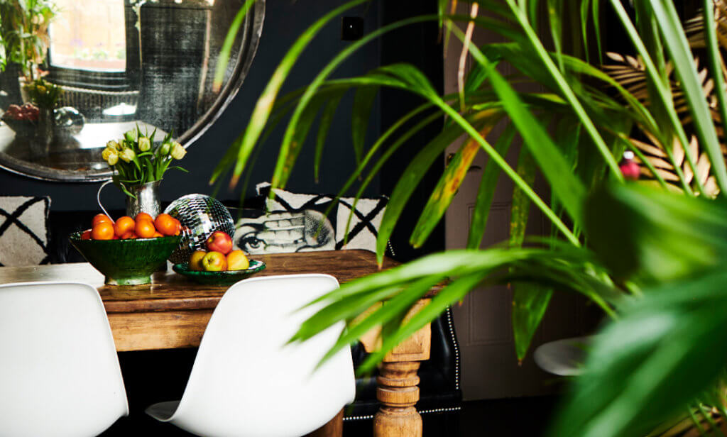 Image of a dark dining room with large circular mirror, green plants, wooden table and white dining chairs.
