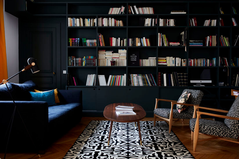 A cosy seating area off the main sitting room featuring a deep grey linen sofa, mid-century style chairs and a graphic black and white print rug. As featured in Rockett St George:Extraordinary Interiors