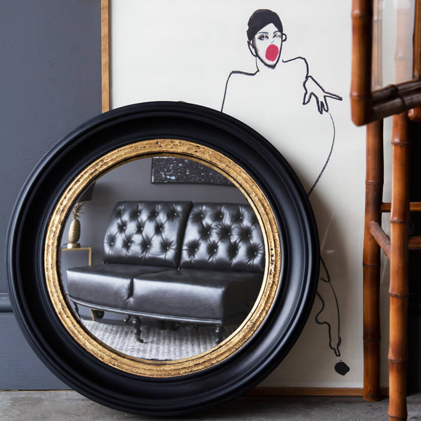 large round gold and black mirror with artwork in the background