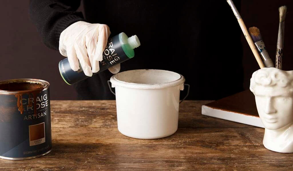 Craig & Rose paint solution being poured into a bucket.