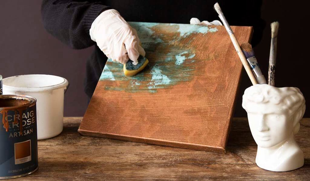 Craig & Rose Artisan copper Patina Solution being brushed with a sponge onto a canvas to reveal an oxidised effect.