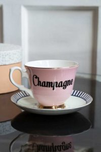 lifestyle image of cute Christmas stockings ideas - pink teacup and saucer with the words champagne across the centre