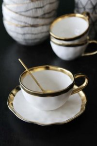 lifestyle image of gold rim shell shape teacup and saucer