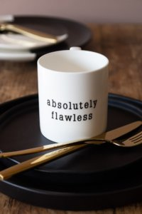 lifestyle image of white mug with the words absolutely flawless
