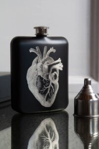 lifestyle image of Black Hip Flask With Laser Etched Heart