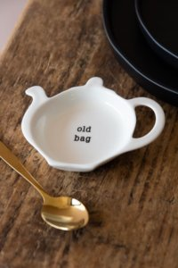 lifestyle image of cute Christmas stockings ideas - teapot shaped tea tidy saucer for old tea bags
