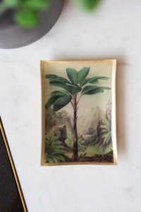lifestyle image of gold trinket tray with a tropical palm tree design