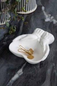 lifestyle image of cute Christmas stockings ideas - white ceramic heart in hands trinket dish