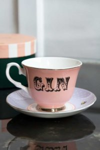 lifestyle image of pink teacup and saucer with gin across the centre