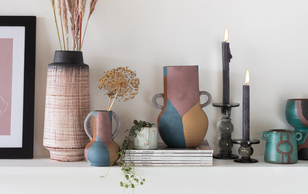 vases, candles and ornaments of different heights on a shelf