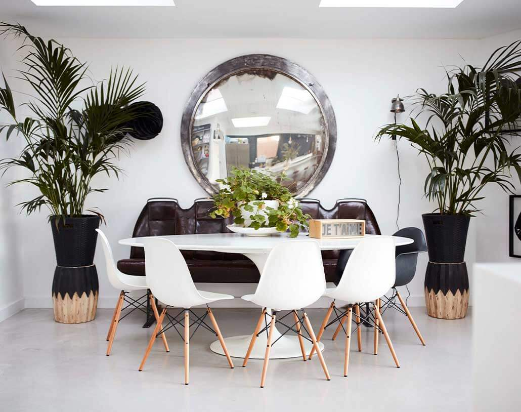 large round mirror used above a dining table, creating drama