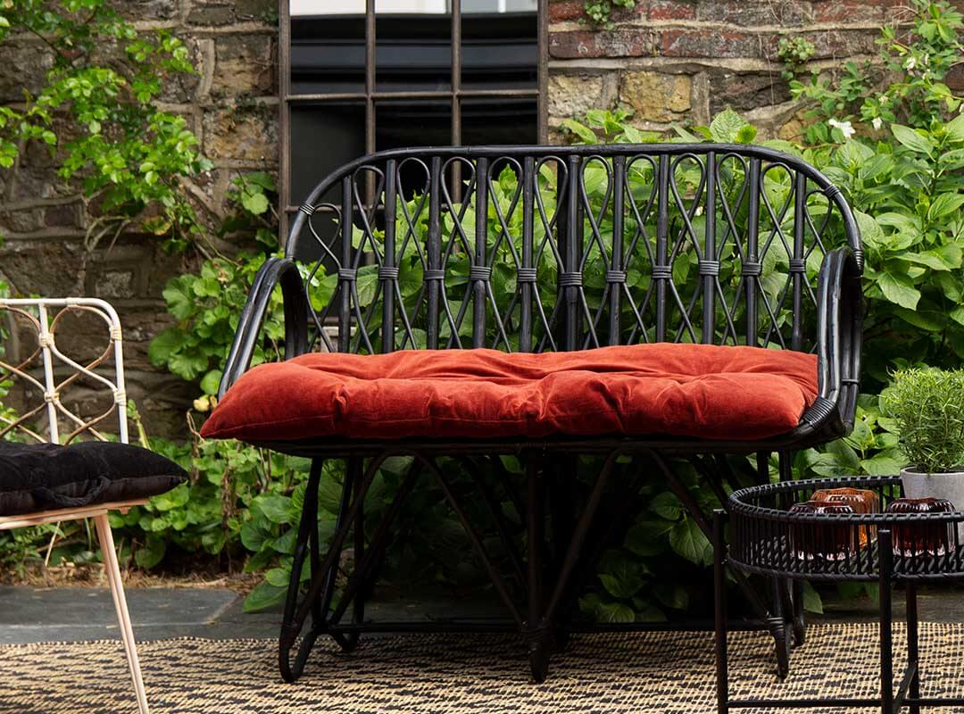 Black rattan bamboo garden bench seat with rust orange cushion