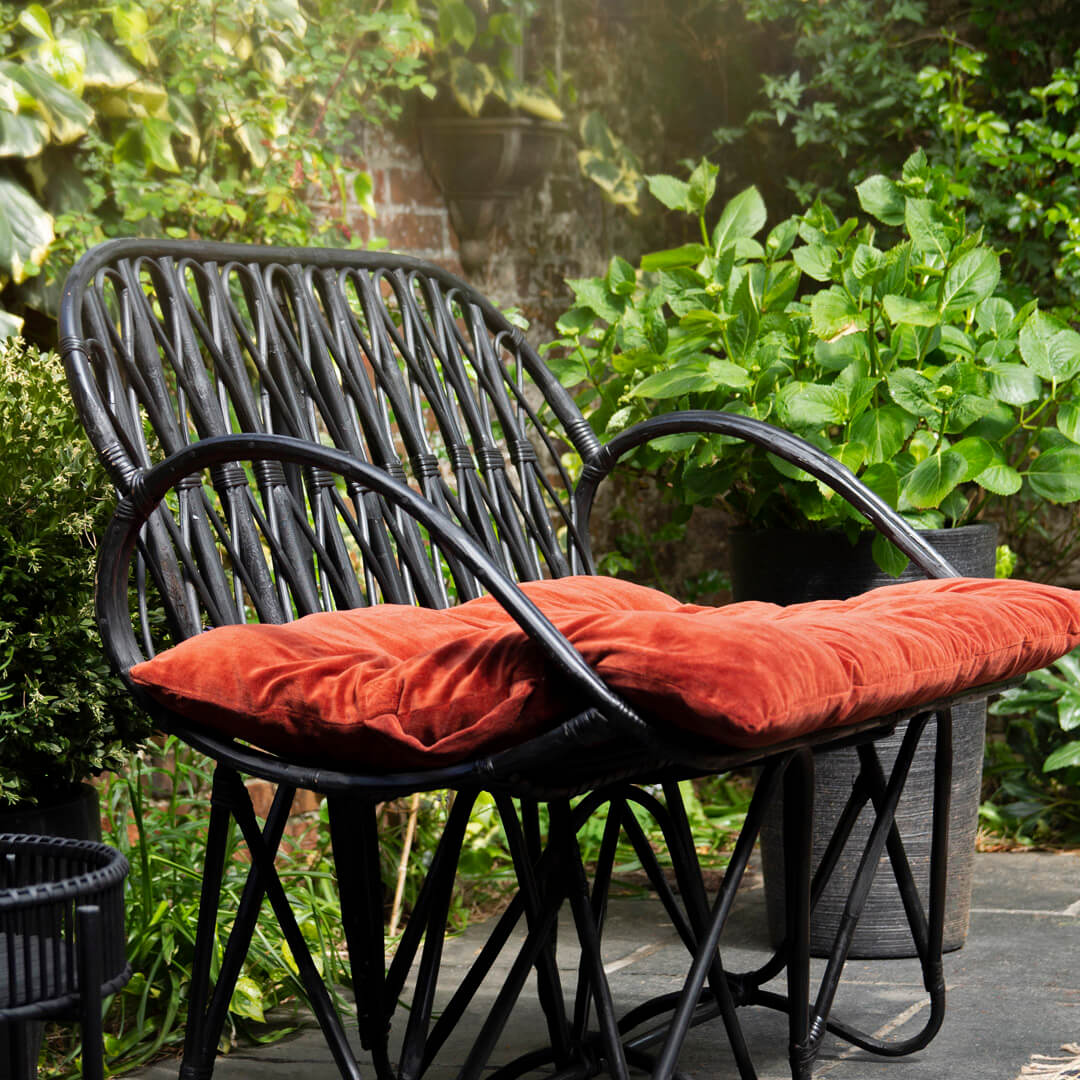 lifestyle image of black bamboo chair in the garden