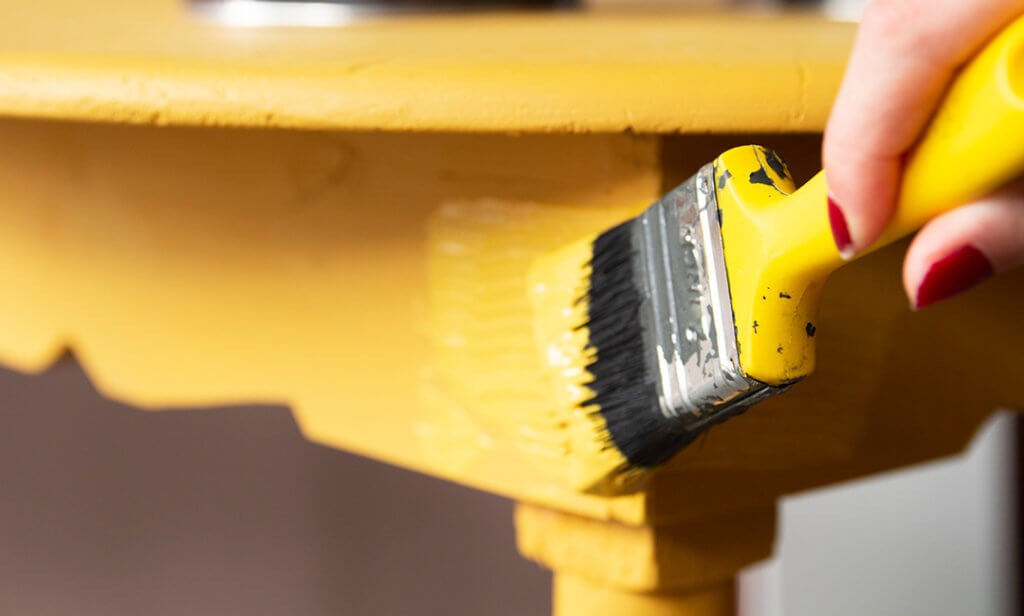 image of a hand holding a paint brush painting a table yellow