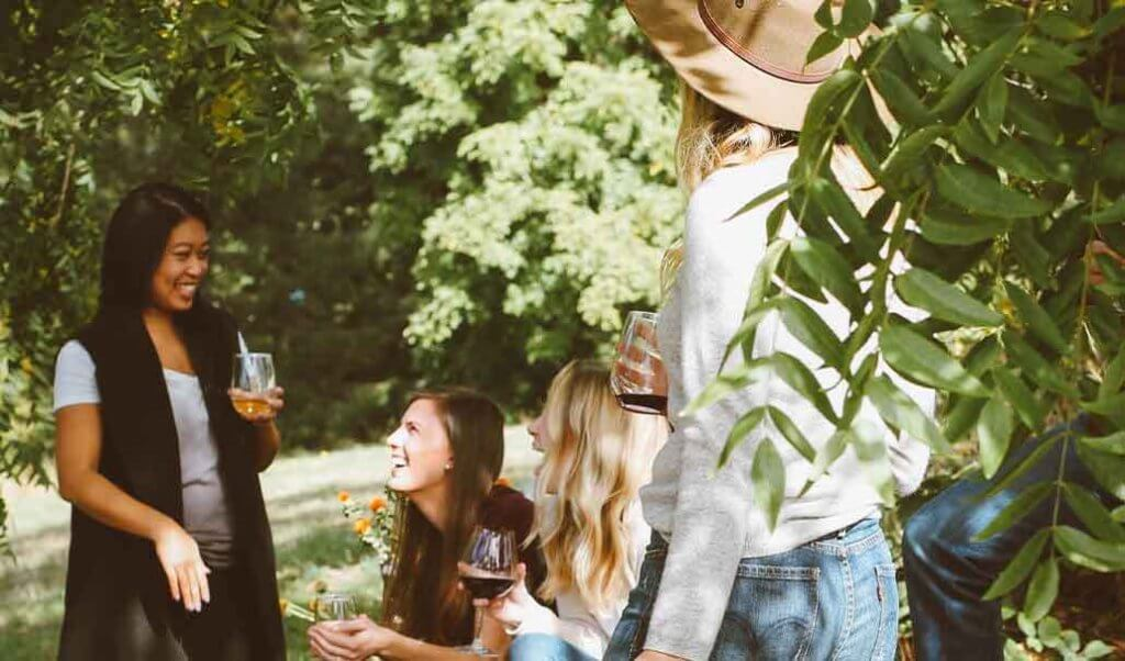image of friends outside with cocktails laughing.