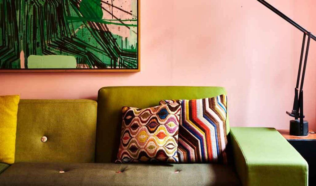 image of a living room with bright pink walls and a green sofa with decorative cushions