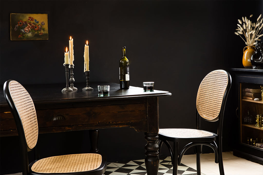 dark interiors dining room with french cafe style woven chairs