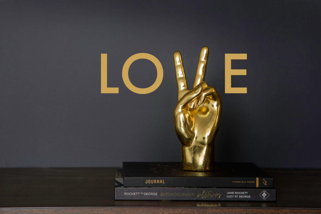 Image of the gold peace hand ornament with the word 'Love'.