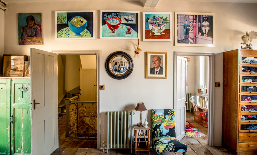 lifestyle image of an eclectic interior with artwork on the walls and pop of pattern