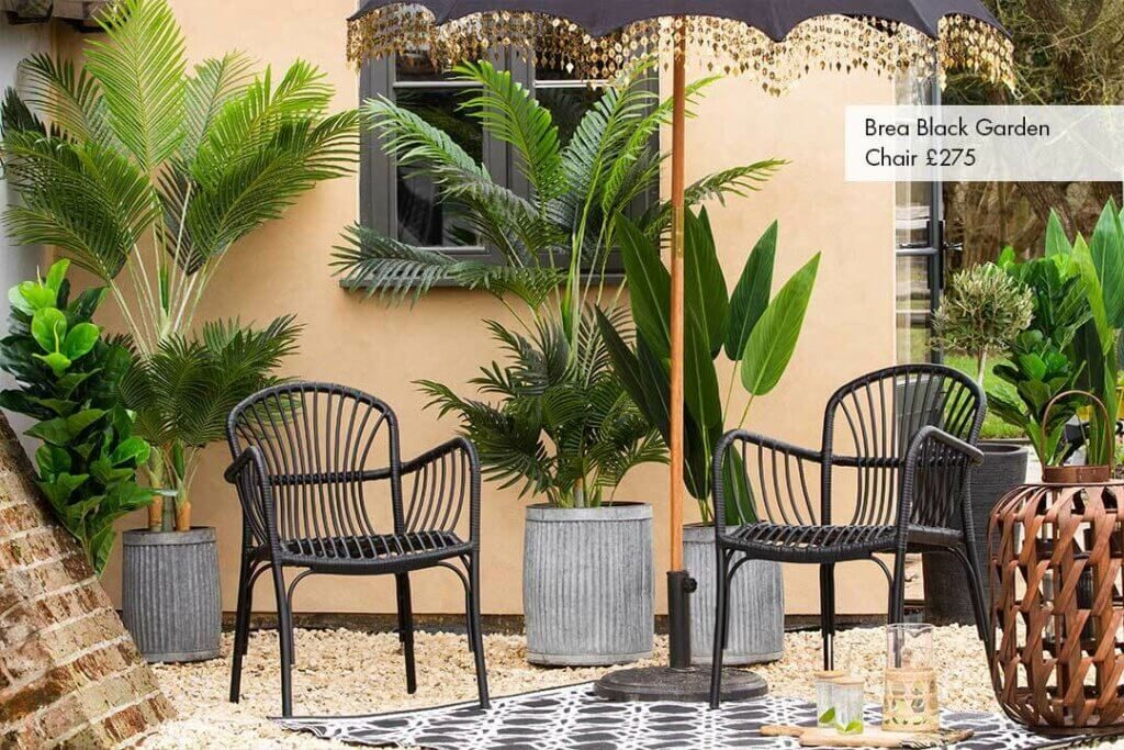 Outdoor space with black brea garden chairs, large leafy plants, a parasol and garden rug.