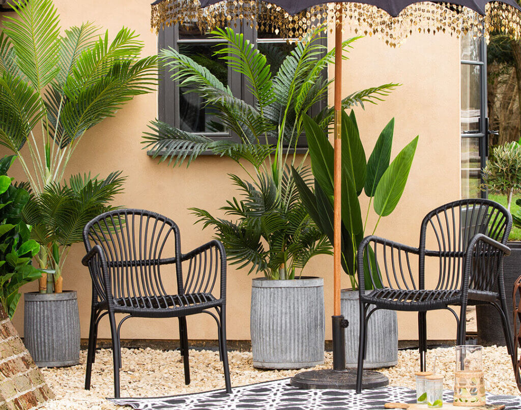 image of an outdoor garden space with two black garden chairs, a garden parasol and beautiful green plants.