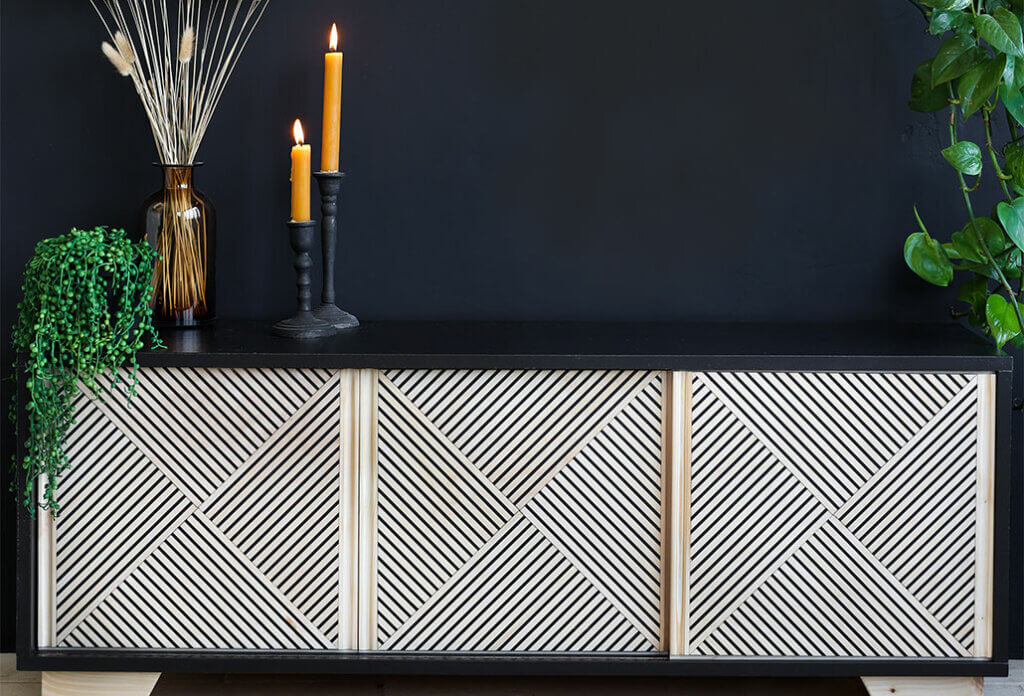 sideboard with 3 drawers and geometric design against dark background. Sideboard is styled with candlesticks and faux plants.